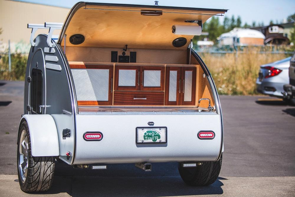 White teardrop camper with door open in parking lot