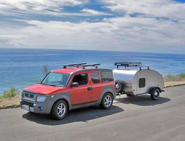 Red SUV pulling silver teardrop camper near water