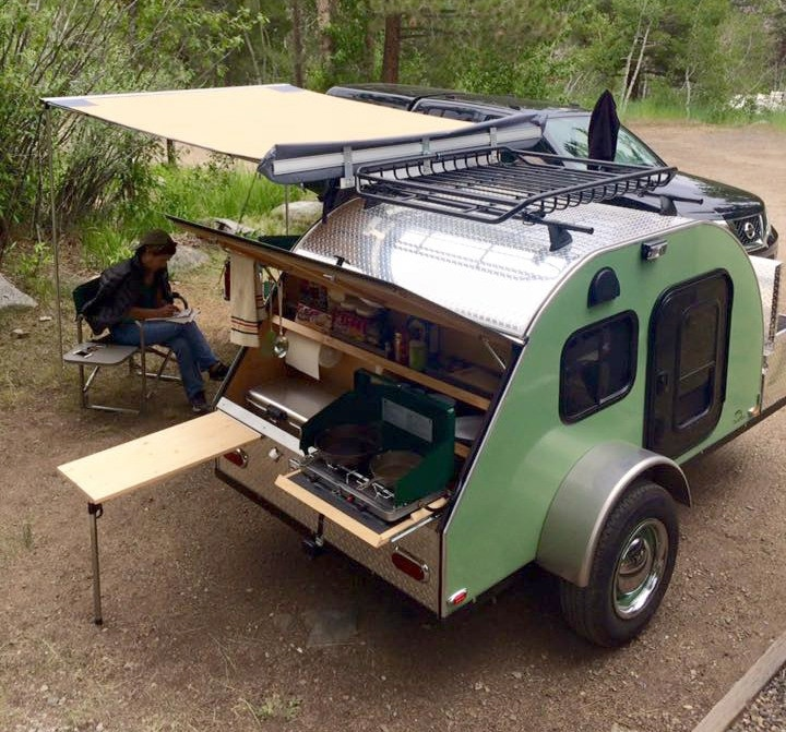 Green teardrop camper with awning and person sitting next to it outside