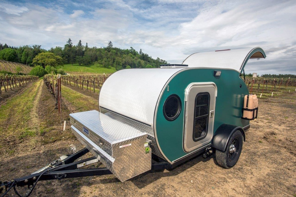 Teal teardrop camper with back door open at vineyards