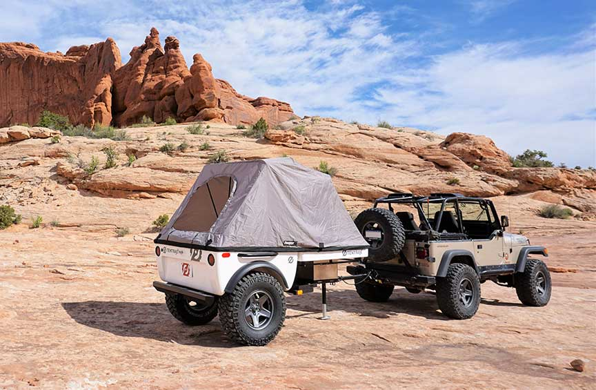 Tentrax trailer and Jeep in front of redrock pinnacles.