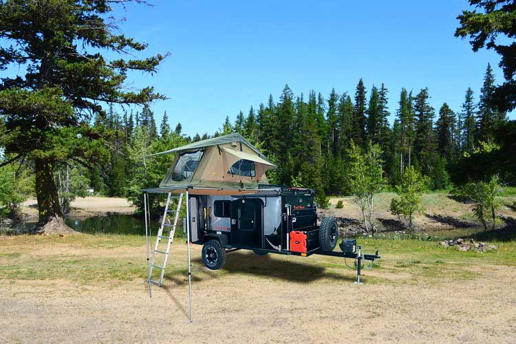 Trail Head trailer with rooftop tent up and evergreen trees behind it.
