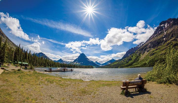 Person sitting on park bench looking over Two Medicine in Waterton Lakes National Park