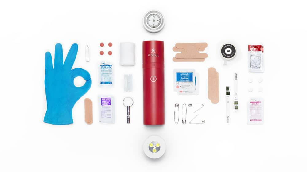 Red and white aluminum VSSL first aid tube with contents inside.