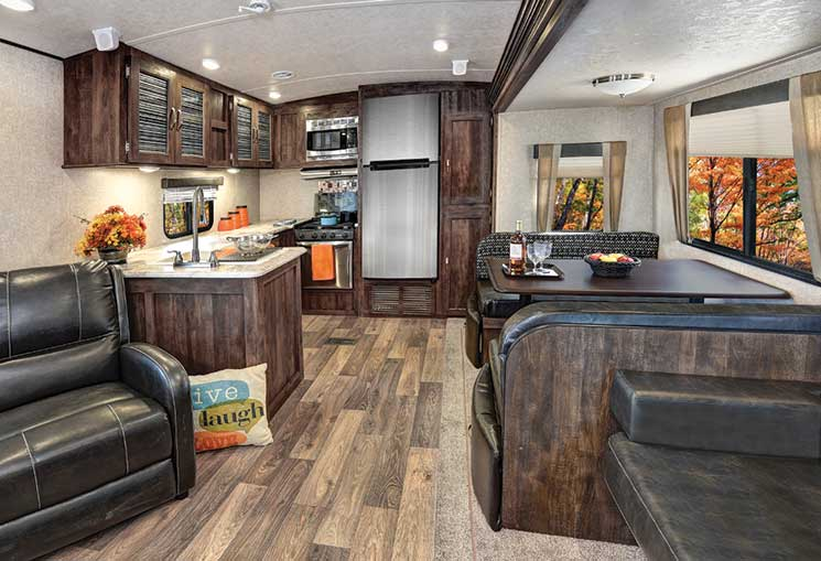 The 34½-foot-long 268RKS, available with an optional exterior kitchen, has residential carpeting in the slide that houses the Deluxe Wood Booth Table Top and jackknife sofa.