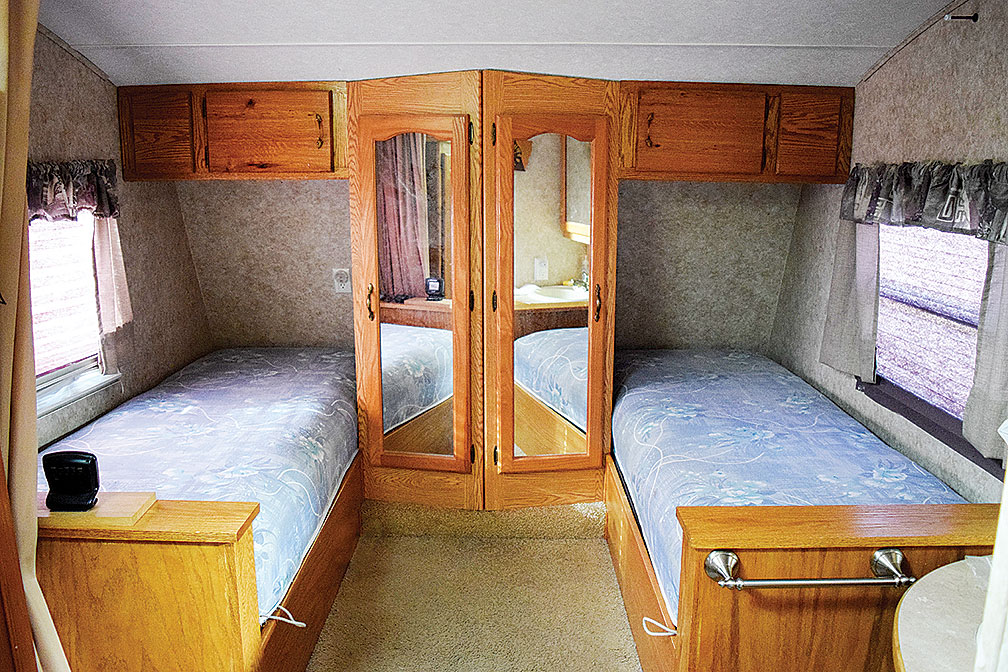 Twin beds in RV with mirrored closets between them