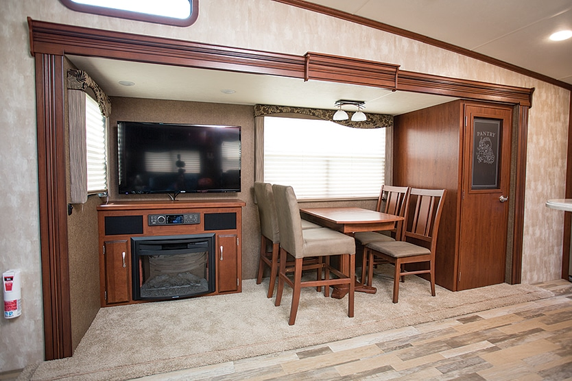 An entertainment center, freestanding table and chairs, and a large pantry tuck nicely into the Latitude's patio-side slideout.