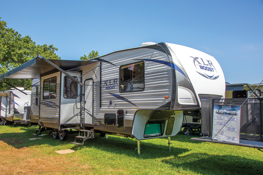 Fifth wheel with awning and slide out parked on grassy area