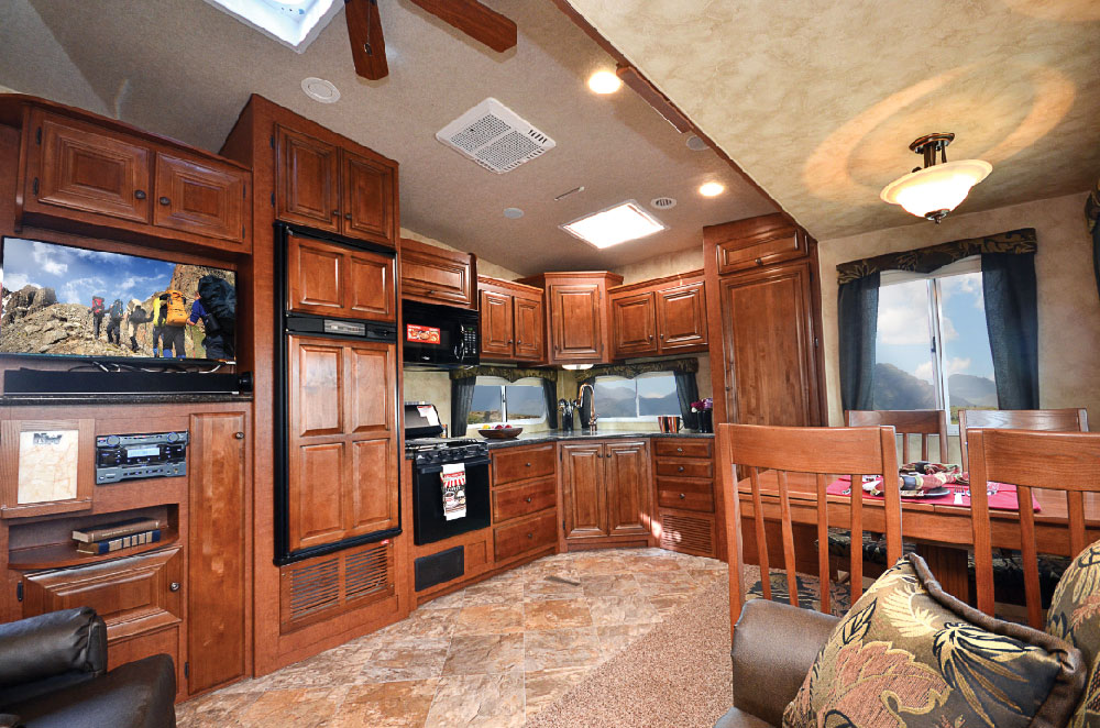 One side of the wide-open living and dining area houses the entertainment  center and the refrigerator, convection microwave and range.