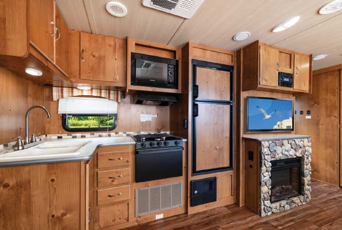 Surprise when you step inside: Warm knotty-pine cabinetry, wood-grain-pattern flooring and a cozy cabin-in-the-woods feel greet you in the 28CRB.