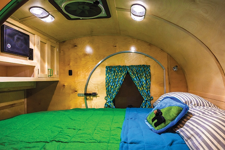 The bed takes up the inside space with a green bedspread, birch walls and two lights overhead.