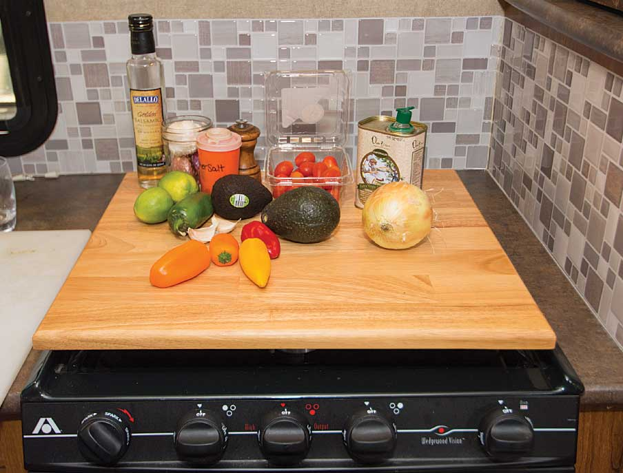 A cutting board stove cover adds extra space to an RV galley