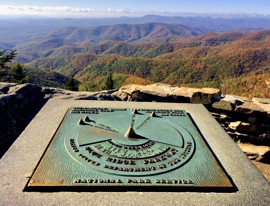Rusty green sundial on concrete slab overlooking canyon staying Devils Courthouse, along Blue Ridge Parkway