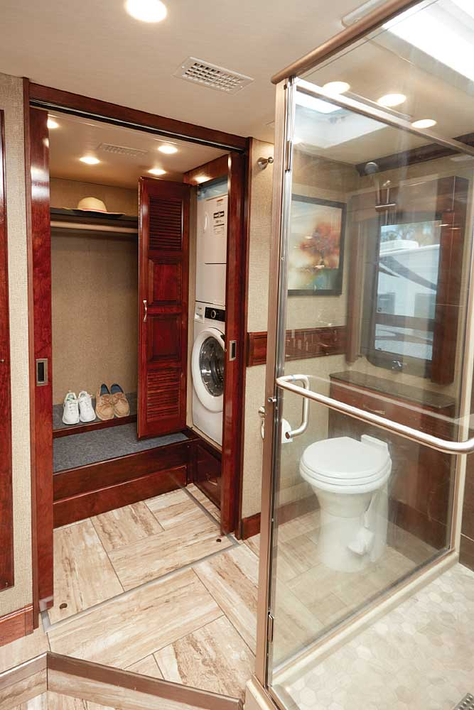 Spacious master bath carries the open feel with a glass-enclosed shower and excellent lighting. A step up leads to toilet and large closet housing washer and dryer.