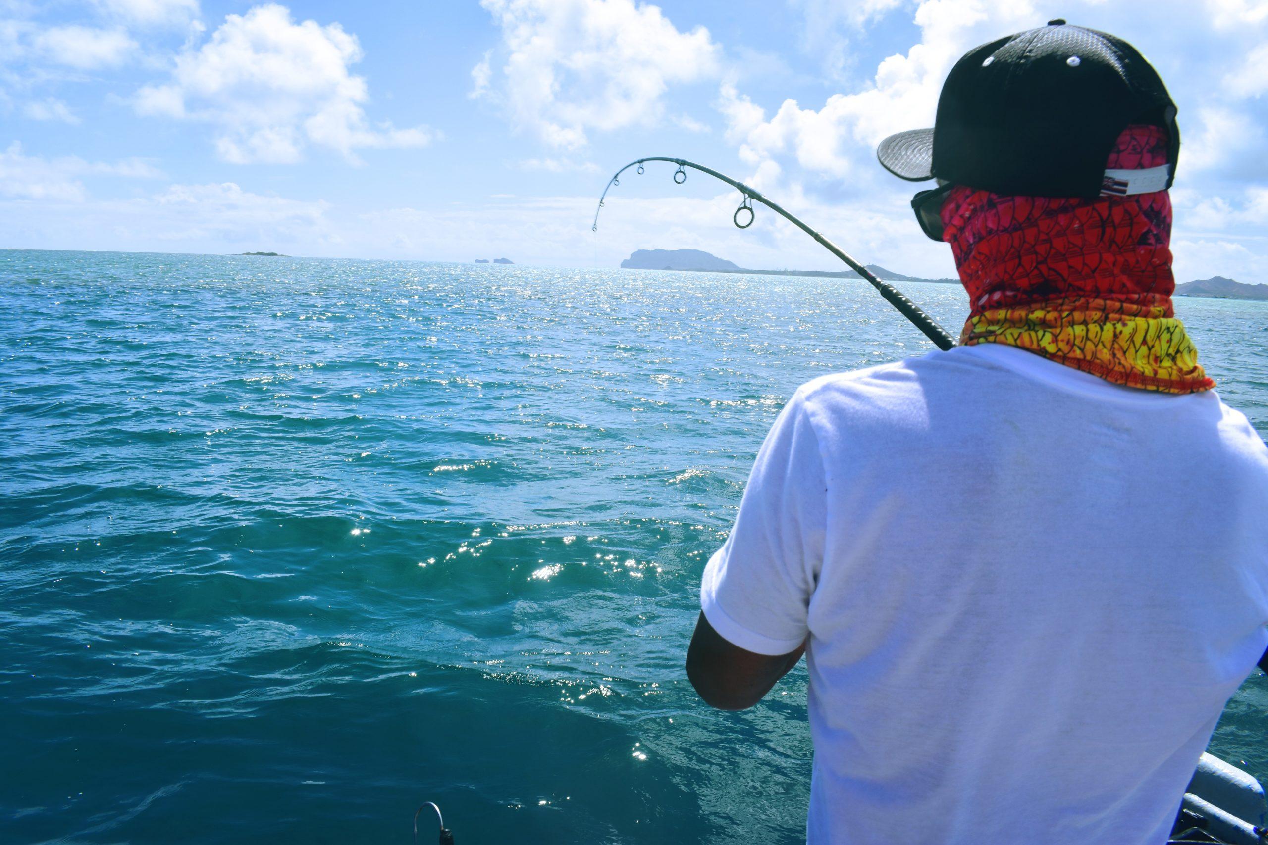 Young man wearing red bandana and baseball hat fishing at Kaneohe Bay