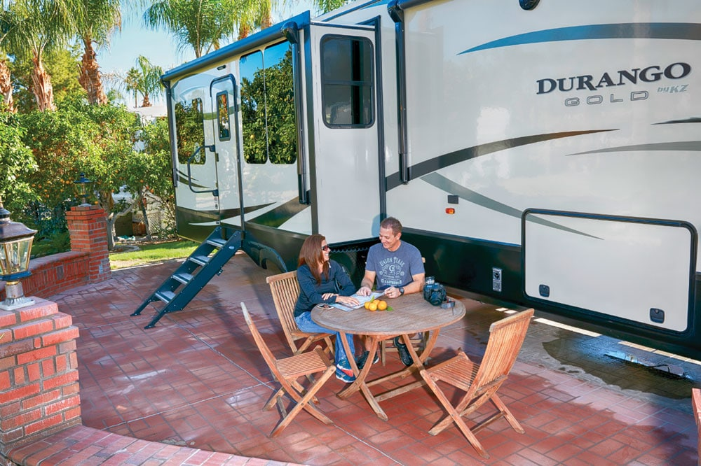 Couple sitting at outdoor table next to large Durango RV