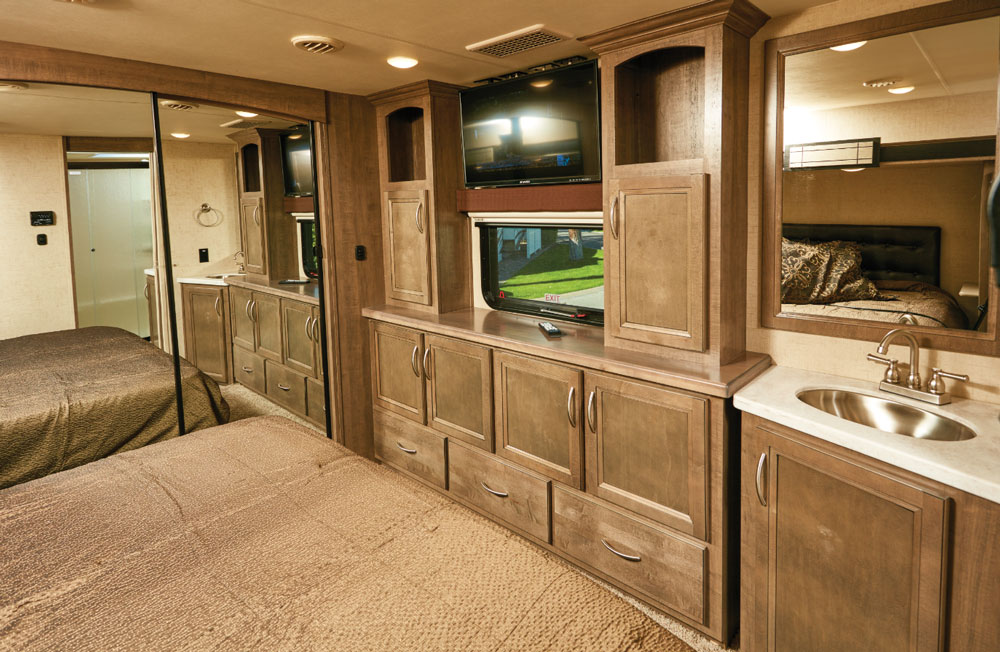 A king-size bed and a generous assortment of cabinets in RV