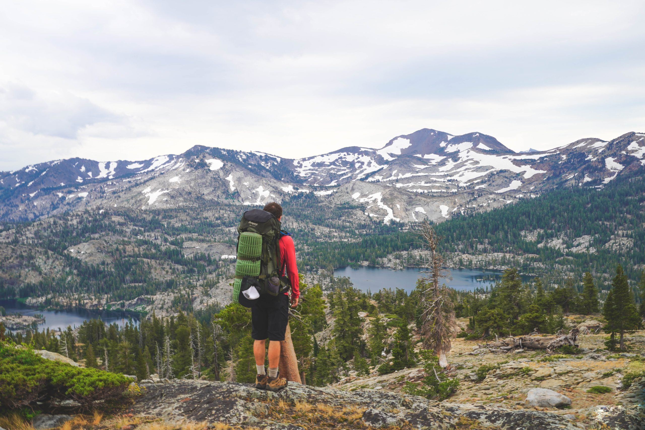 Hiker standing on ledge looking over Lake Tahoe