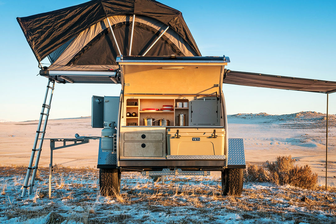 Rear view of Escapod Top trailer with galley hatch open and rooftop tent extended.
