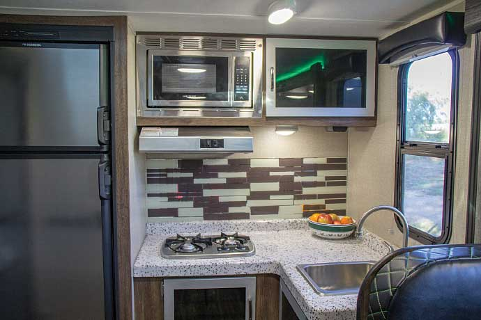The kitchen packs in ample counter space and cabinetry, and has a 6-cubic-foot fridge.
