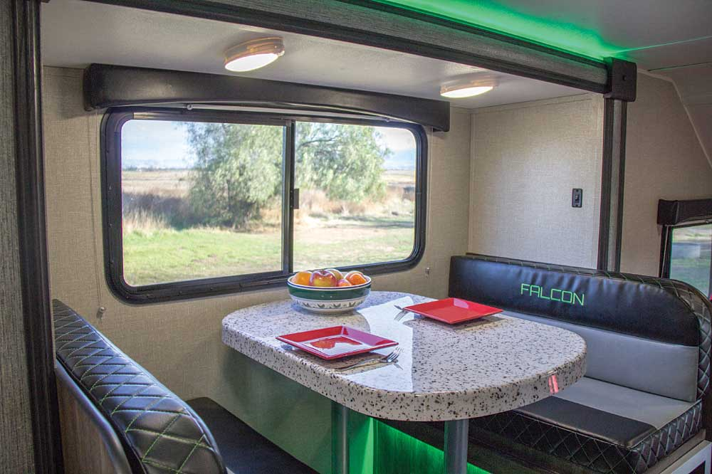 Individually controlled LED light fixtures are positioned throughout the interior. The dinette is accented with green LEDs above and below and a large sliding window.