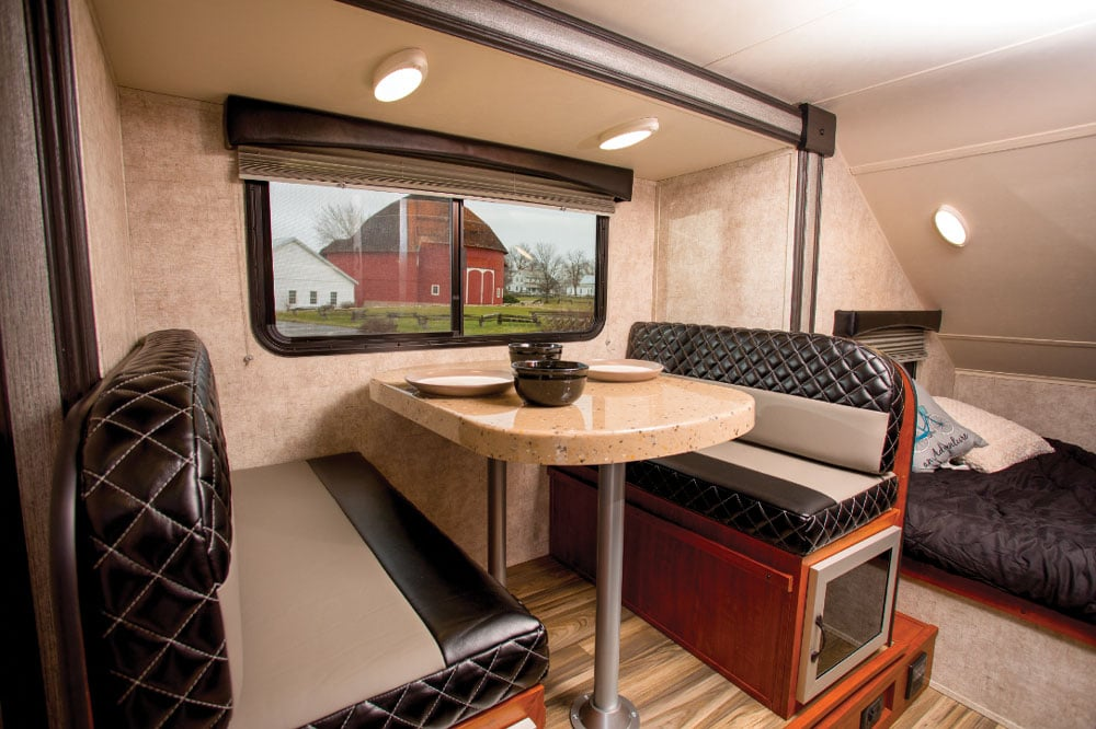 The step-up dinette is housed in a slideout, and the window slides open for good ventilation. Cushions pictured are a leatherlike prototype Travel Lite is considering offering; our test unit had fabric-covered cushions.