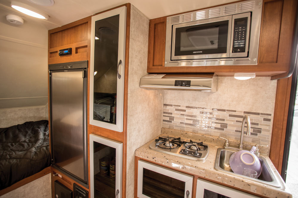 The 5-cubic-foot refrigerator is large for this size trailer, and there's lots of stashing room behind those dark tempered-glass doors.