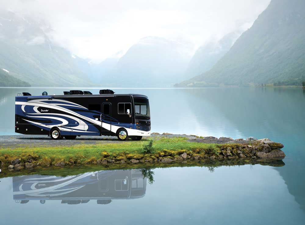 Large black, blue and white motorhome parked along lake with reflection