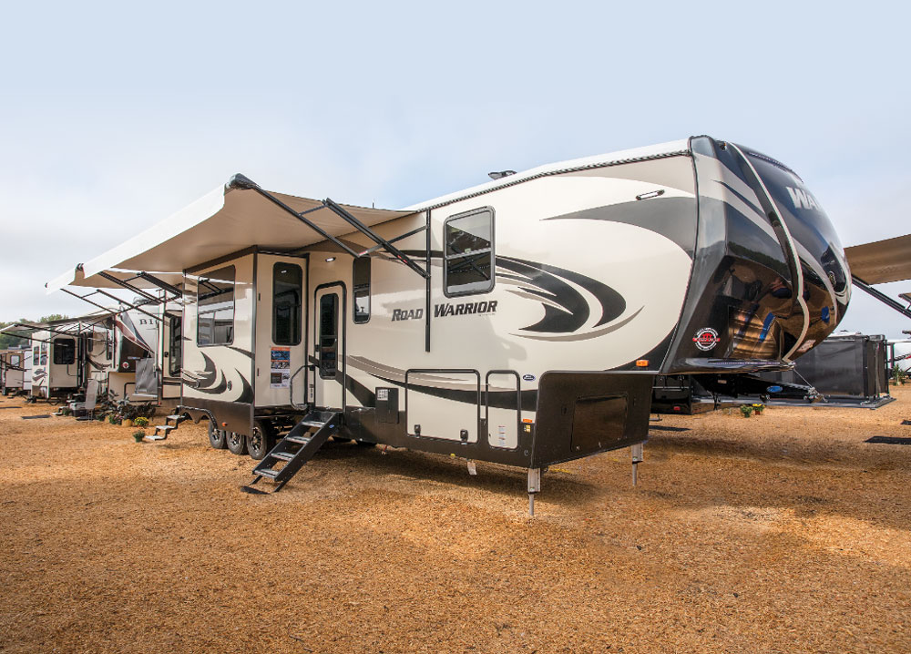 Beige and brown designed Heartland Road Warrior travel trailer with awning out