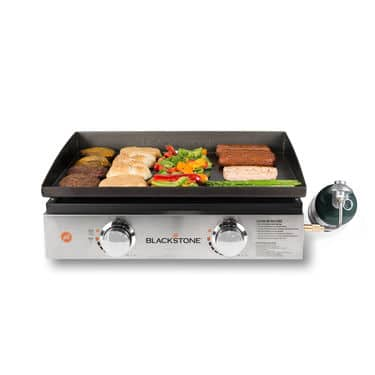 """Blackstone 22"""" Tabletop Griddle holding sausages and burger patties"""
