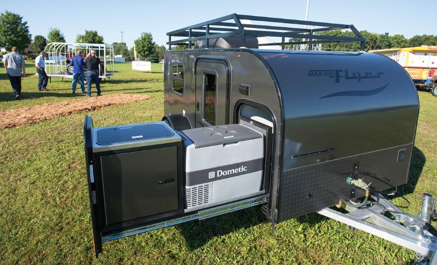 Dark grey tiny travel trailer parked on grassy area