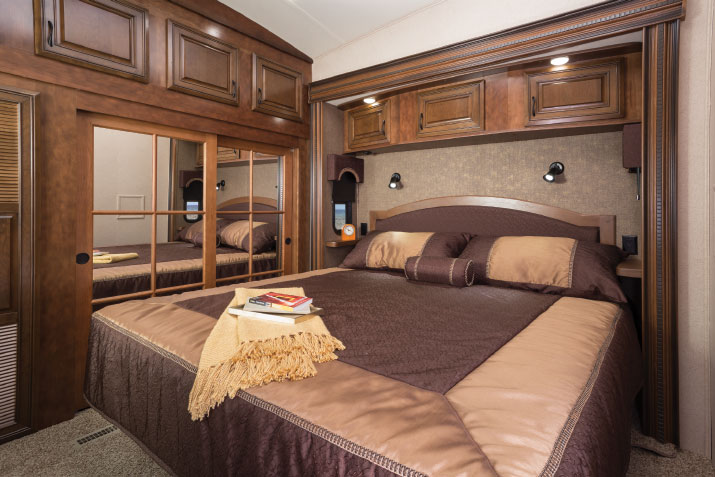 Overhead cabinets, built-in nightstands and the king-size bed's hardwood headboard tuck into the front-bedroom slide.