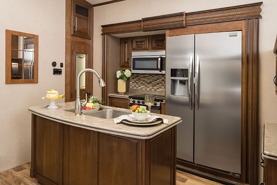 Residential touches include a gooseneck faucet above twin stainless-steel sinks in the kitchen island.
