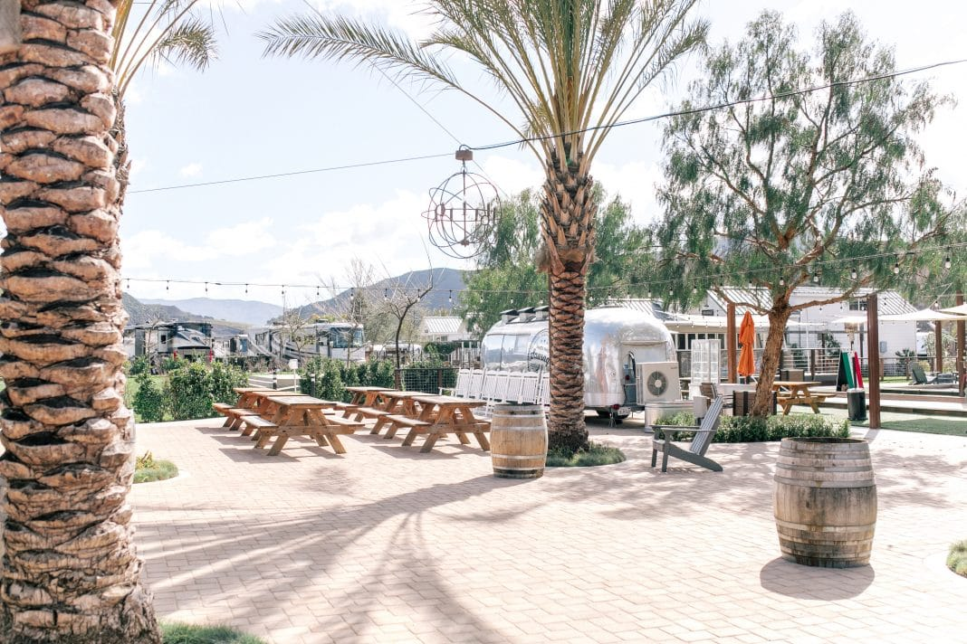 Campsite with silver Airstream and park benches with palm trees