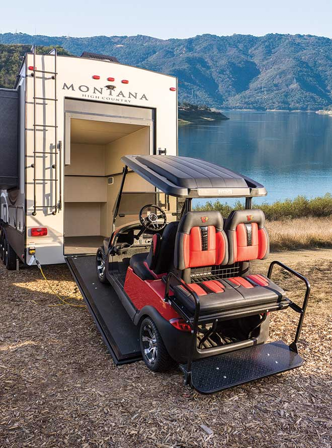 Golf cart on incline of door to back of Montana RV with lake in background