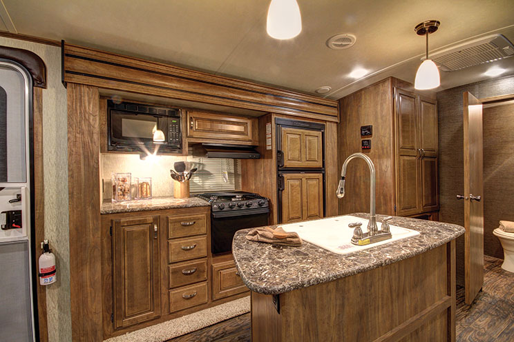 A large sink and high-rise faucet are mounted in an island across from the appliances, storage drawers and cabinets housed in the galley slideout. The rear bathroom is large enough to spread out and has plenty of storage. The living roo