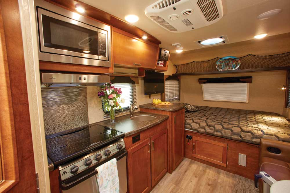 The 1475's spacious galley features a clean look with a glass flush-mounted cover for the range, and attractive cabinetry and decor, including soffit LEDs.
