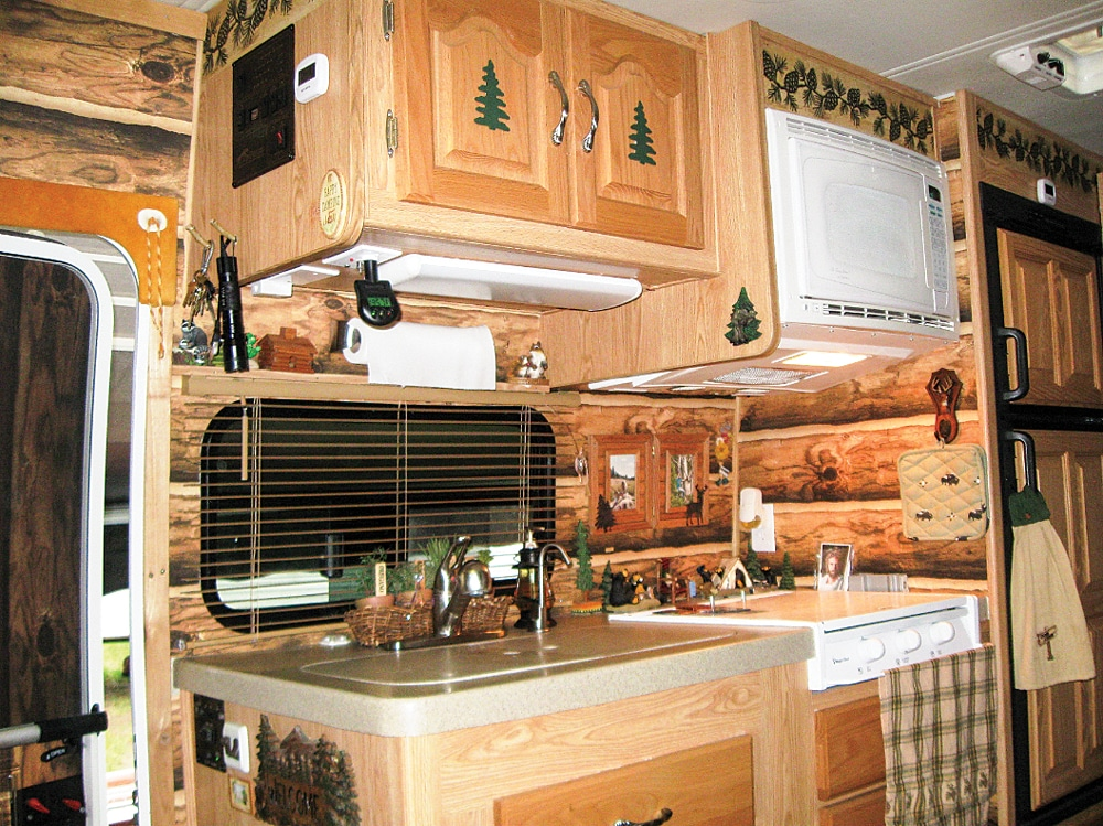 This log cabin makeover is all in the details. From the evergreens on the cabinet doors to the pinecone wallpaper inlay of the kitchen.