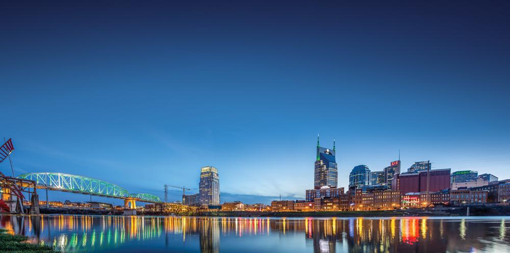 The skyline and John Seigenthaler Pedestrian Bridge reflect in the Cumberland River.