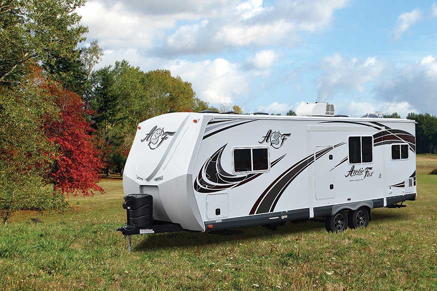 White Arctic Fox fifth wheel RV parked outside