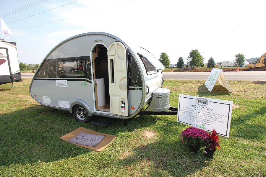 Tiny curved trailer with door open parked on grass