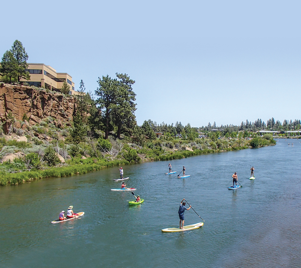 Outdoor enthusiasts paddle and float along the Deschutes River in Bend.