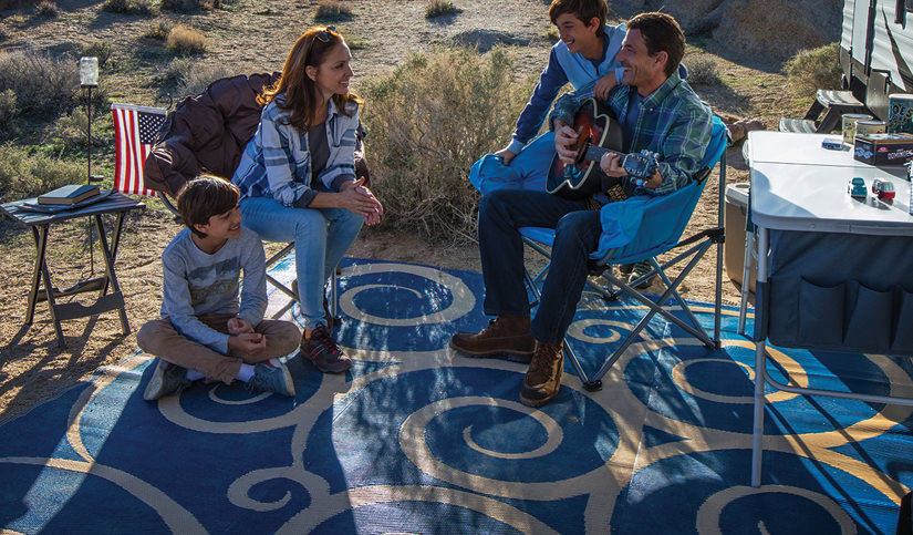 Family camping outdoors, sitting on outdoor rug father playing guitar