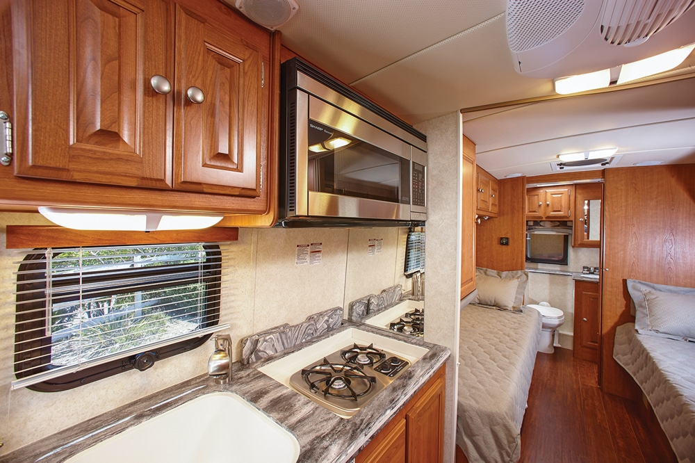 A residential-size microwave convection oven, large sink and pullout cutting board below the two-burner range contribute to simplifying food preparation. An accordion-style door separates the galley from the bedroom with twin-size beds.