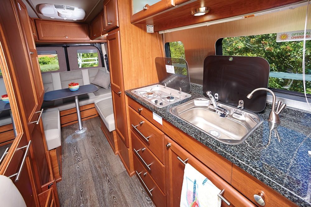 The galley offers ample storage and is highlighted by a granite countertop with flush-mounted glass covers for the two-burner cooktop and sink.