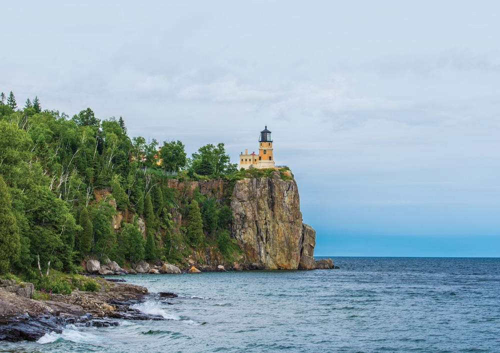 Split Rock Lighthouse , a picturesque landmark, towers above Lake Superior from its cliff-top perch.