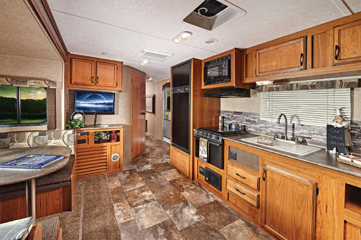The Launch's ample kitchen counter reaches from the three-burner range and double-bowl sink to the back of the trailer.