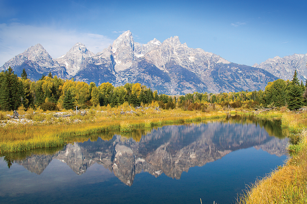 The Snake River mirrors the majestic Grand Tetons, photographed from Schwabachers Landing Road. With easy river access, the landing is a launch site for river rafters and anglers.