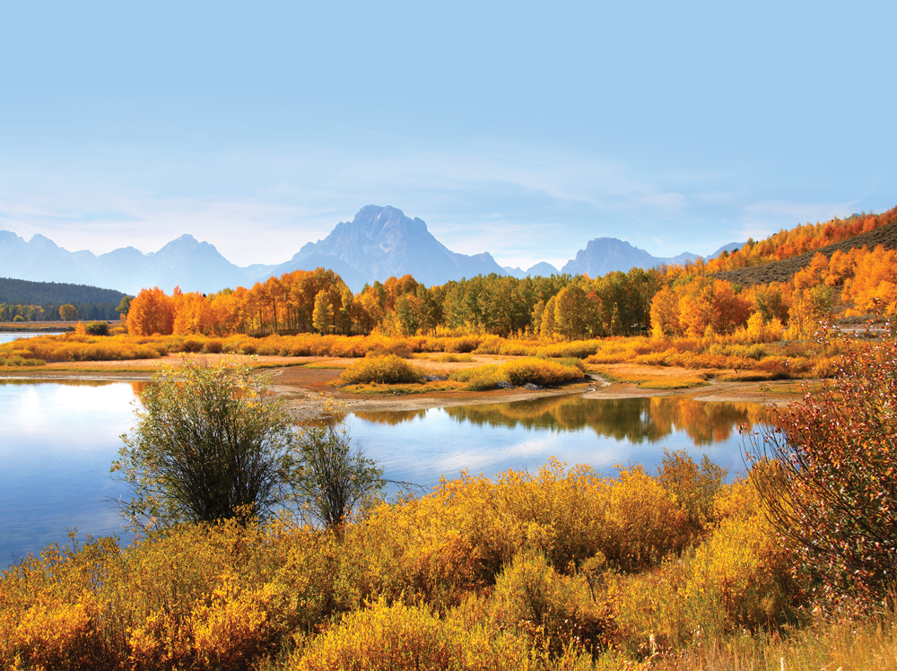 Christian Pond near Oxbow Bend reflects  spectacular mountains and changing colors. Once winter is over, the shallow pool warms up and attracts many types of wildlife that include a variety of birds and moose.