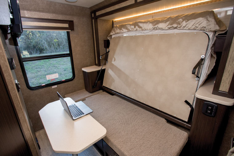 Beneath the folded bed, left, is a cushioned seating area and mounting point for the table, creating a workspace illuminated by the large window at the rear of the coach.